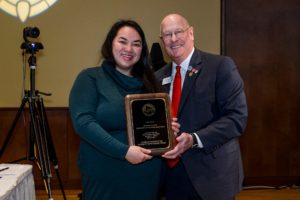 Bee Vang holds award with group