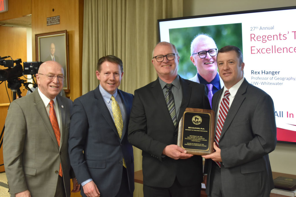 Photo of UW-Whitewater Professor Rex Hanger (second from right) receiving a UW System Board of Regents 2019 Teaching Excellence Award at the UW System Board of Regents meeting held in Madison on April 5, 2019. Also pictured (from left:) UW System President Ray Cross, Regent President John Robert Behling, and Regent Jason Plante.