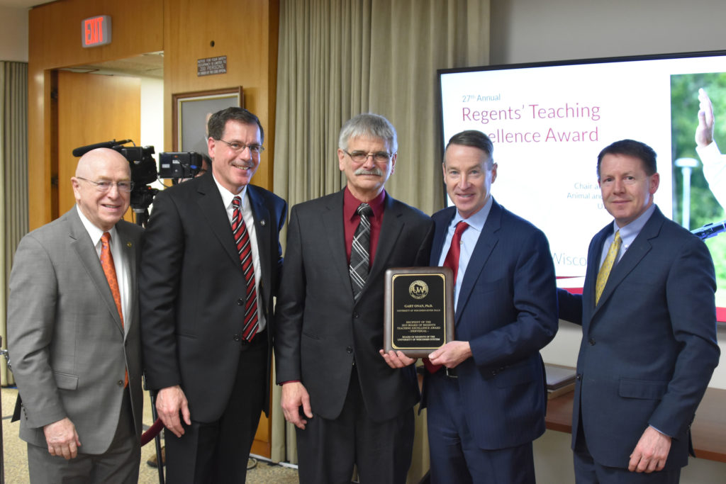 Photo of Gary Onan, Chair and Professor of Animal and Food Science at UW-River Falls (center), receiving a UW System Board of Regents 2019 Teaching Excellence Award at the Board of Regents meeting held in Madison on April 5, 2019. Also pictured (from left): UW System President Ray Cross, UW-River Falls Chancellor Dean Van Galen, Regent Mike Jones, and Regent President John Robert Behling.