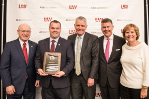 Photo of Mark Klapatch (holding plaque) receiving a Board of Regents 2019 Academic Staff Excellence Award; also pictured (from left) UW System President Ray Cross, Regent Bob Atwell, Regent Drew Petersen, and Regent Janice Mueller