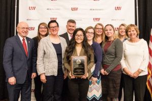 Photo of the UW System Board of Regents 2019 Academic Staff Excellence Award in the Program category being awarded to the UW-Parkside Library. (from left) Ray Cross, UW System President; Laura Briskie, Research Help and Instruction Librarian; Anna Stadick, Library Director; Regent Drew Petersen; Xou Lee Va Vang, Research Help and Instruction Librarian; Paige Barreto, Outreach and Marketing Librarian; Dina Kaye, Head of Library Collections; Melissa Olson, Head of Archives; Rebecca Robbennolt, Archivist and Records Manager; and Regent Janice Mueller (not pictured) Heather Spencer, Access Service Technology Coordinator; Liz Antaramian, Library and Archives Assistant; Dave Gehring, Access Services Manager; Jay Dougherty, Head of Library Systems; Brian Dorband, Acquisitions Supervisor; Jennie Callas, Head of Reference and Instruction; Becky Tolejano, Library Technology Support; Shauna Edson, Instructional Design Librarian; and Jean Hrpcek, Administrative Assistant