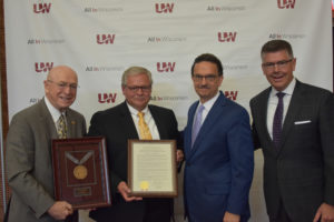 Photo of Regent Emeritus S. Mark Tyler accepting his resolution of appreciation, pictured with from left, President Ray Cross, Interim Vice President of Corporate Relations and Economic Engagement David Brukardt, and Regent President Andrew S. Petersen