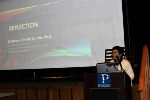Dr. Carleen Vande Zande speaking at lectern.