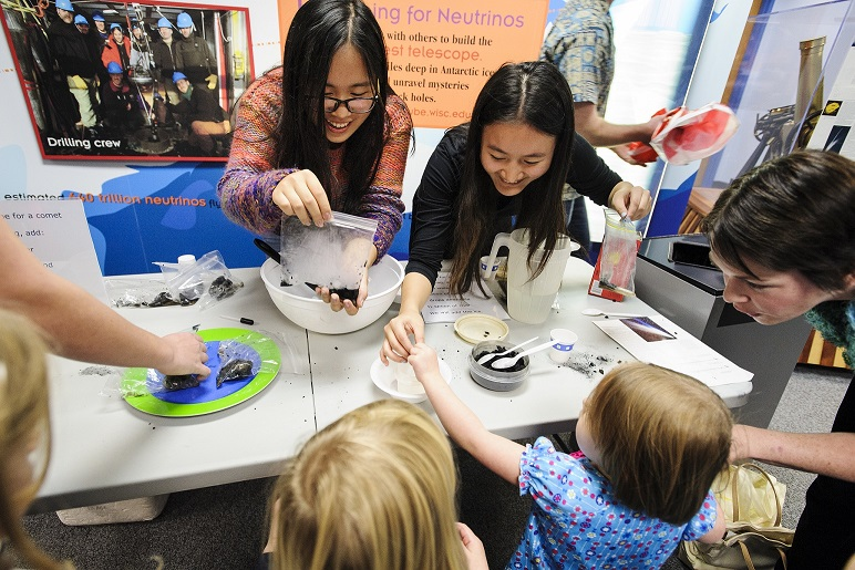 Undergraduates and UW Astronomy Club members Lin Shi, left, and Zishan Xia demonstrate how to use a mix of water, sand, ammonia, coal and dry ice to make comet material during Family Science Night at UW Space Place at the University of Wisconsin-Madison on Nov. 22, 2013. The science outreach event, presented by South Madison Promise Zone and UW Space Place, attracted more than 400 people to engage in hands-on experiments and exhibits ranging from astronomy to zoology. (Photo by Jeff Miller/UW-Madison)