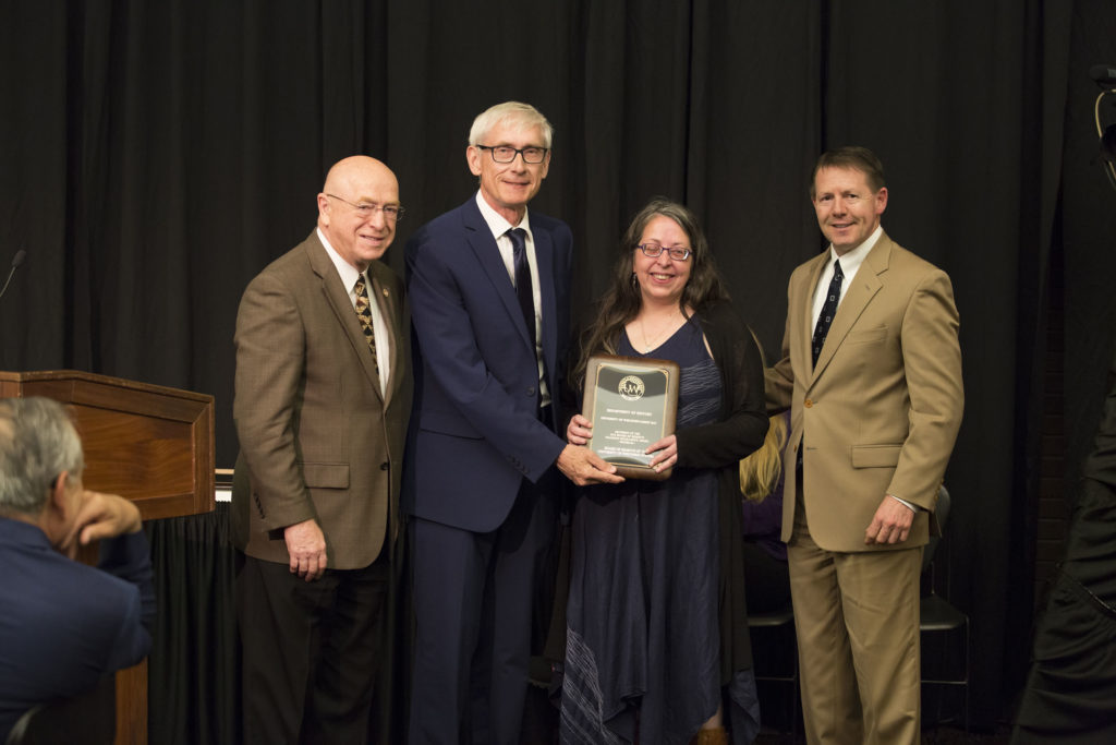 Photo of (from left) President Ray Cross, Regent Tony Evers, Dr. Heidi Sherman (department chair), and Regent President John R. Behling